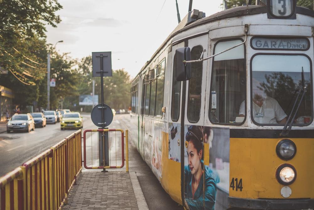 white train beside yellow steel fence