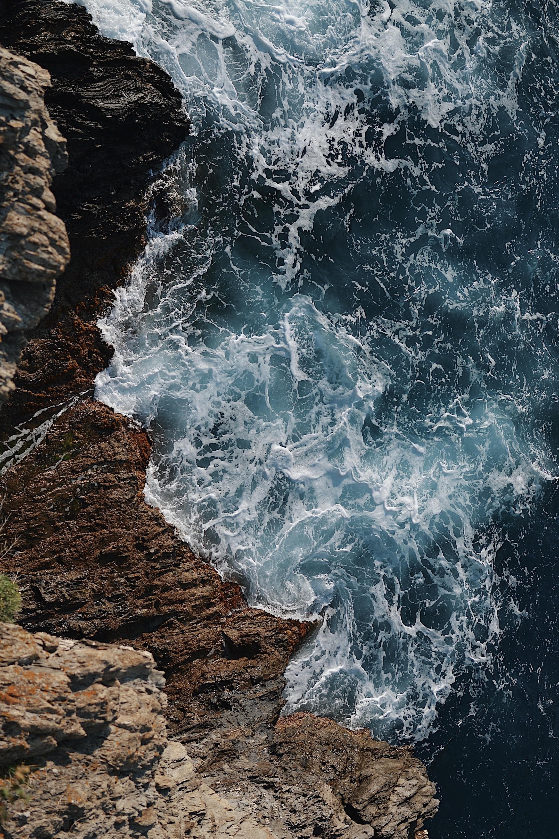 waves splashing on gray rocky cliff during daytime