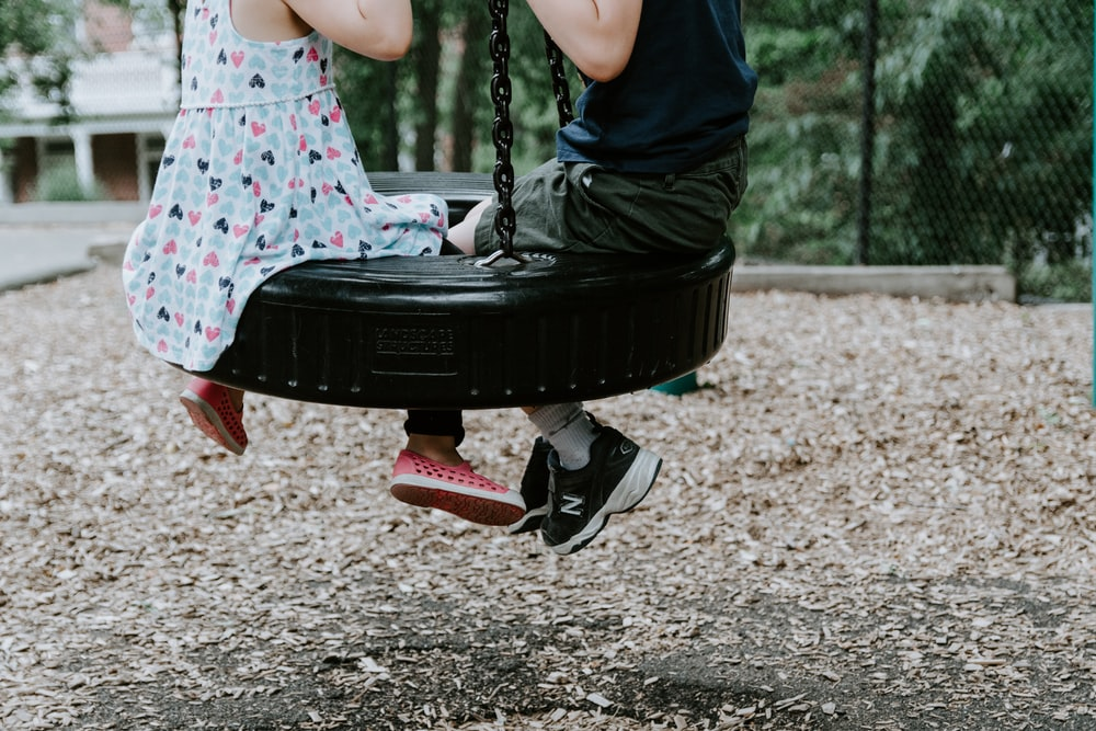 two children playing on tire swing
