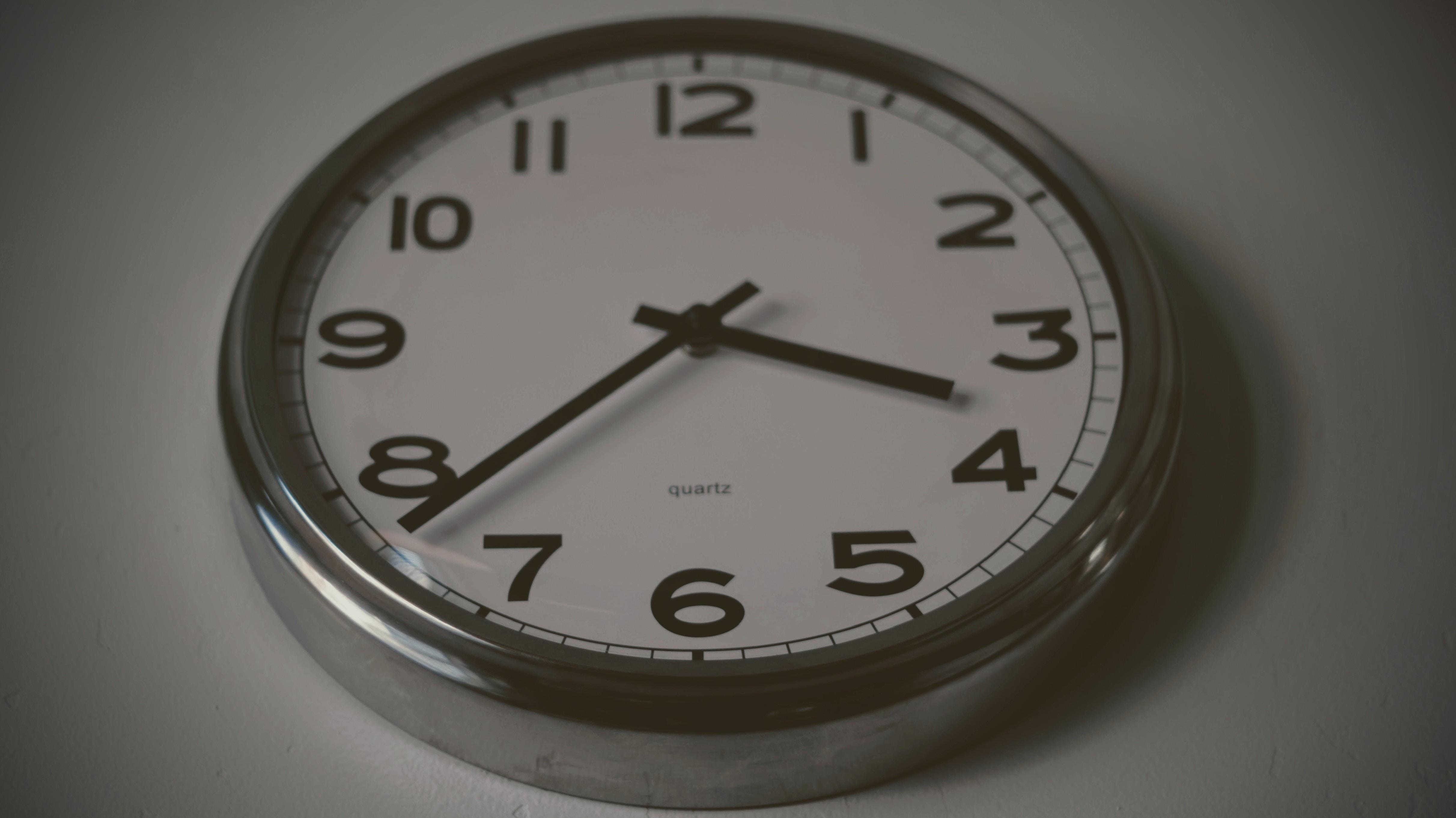 round silver wall clock at 3:38