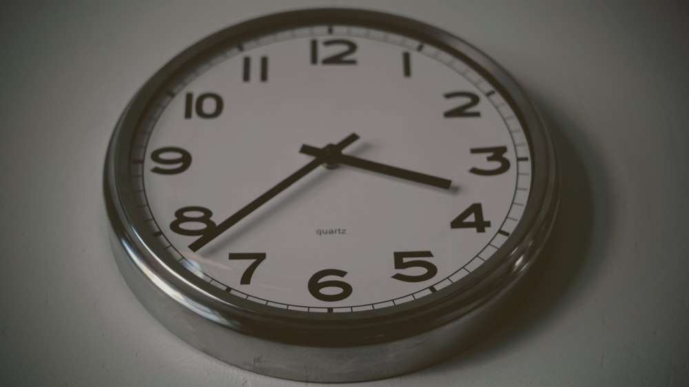 round silver wall clock at 3:38