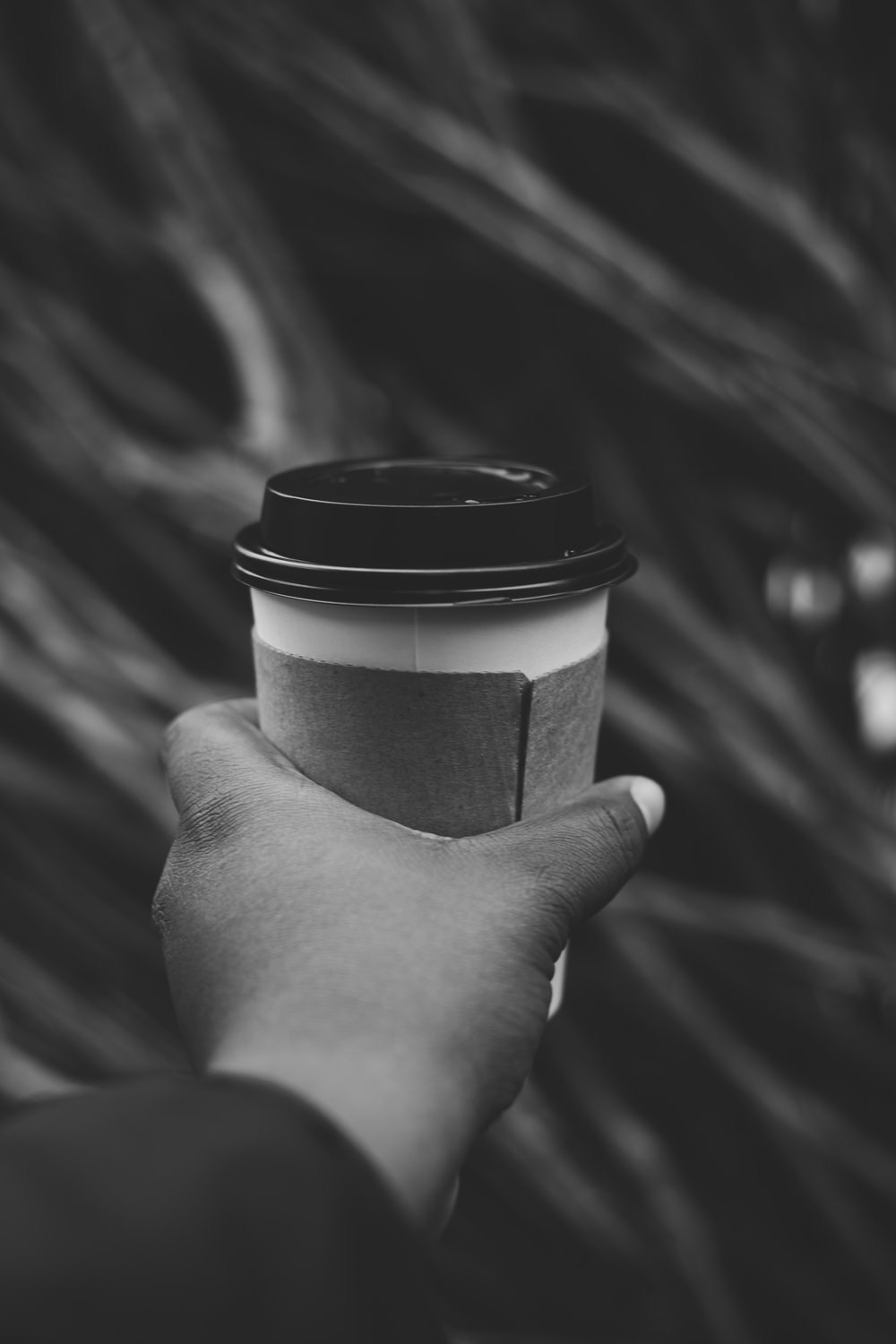 grayscale photo of person holding disposable cup