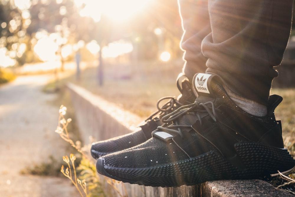 b1ec0d8dea73 person wearing pair of black adidas sneakers