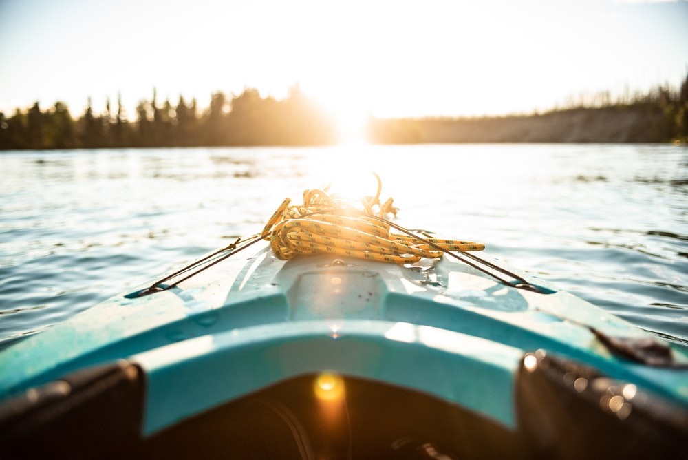 blue kayak on body of water during golden hour