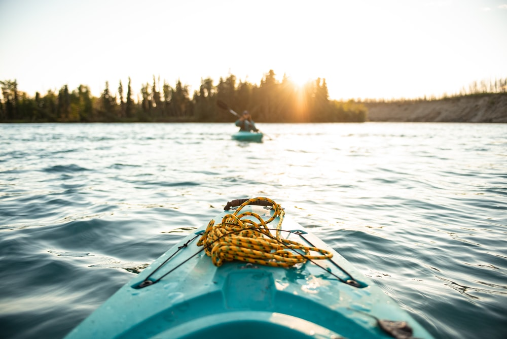 person silhouette photo of person on-board in green kayak near other person in green kayak