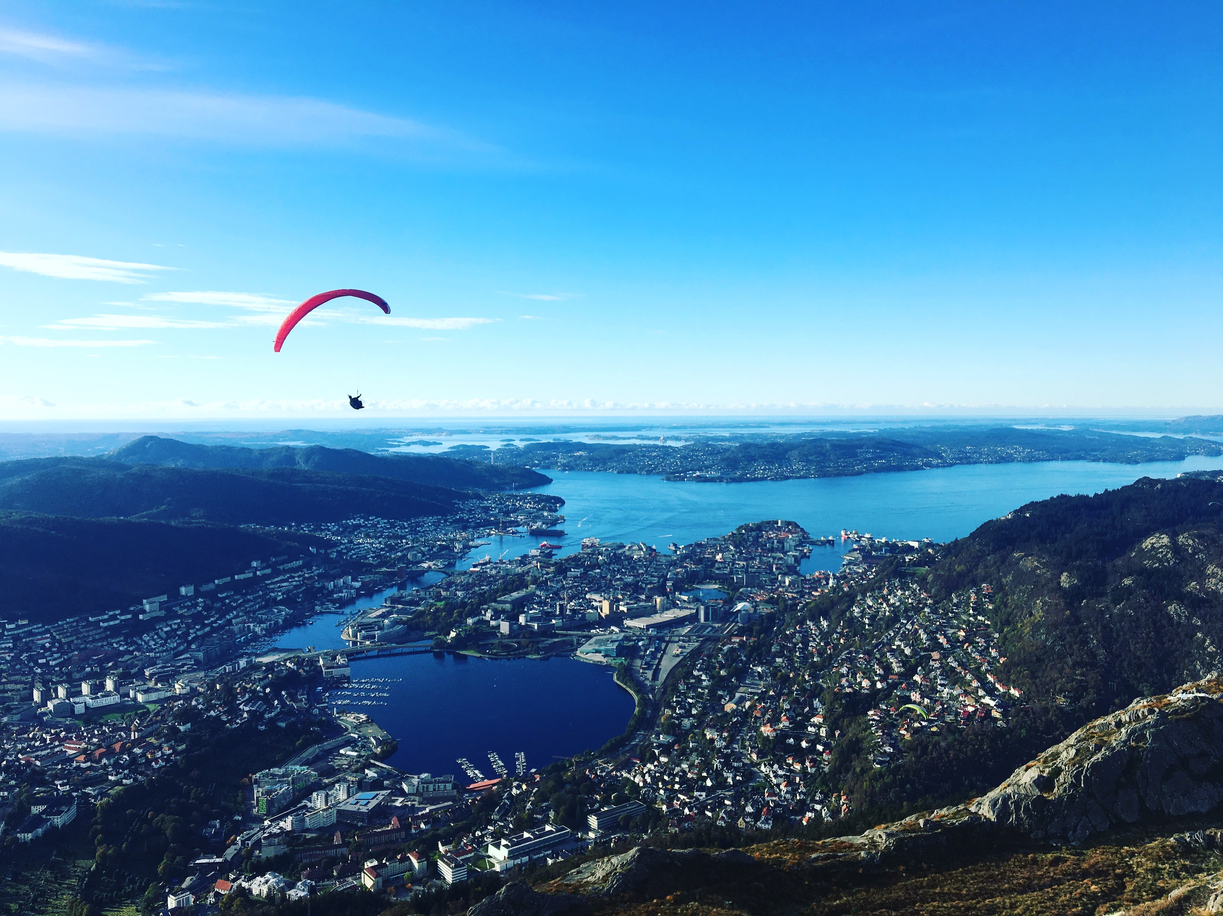 paraglider above buildings and body of water at daytime