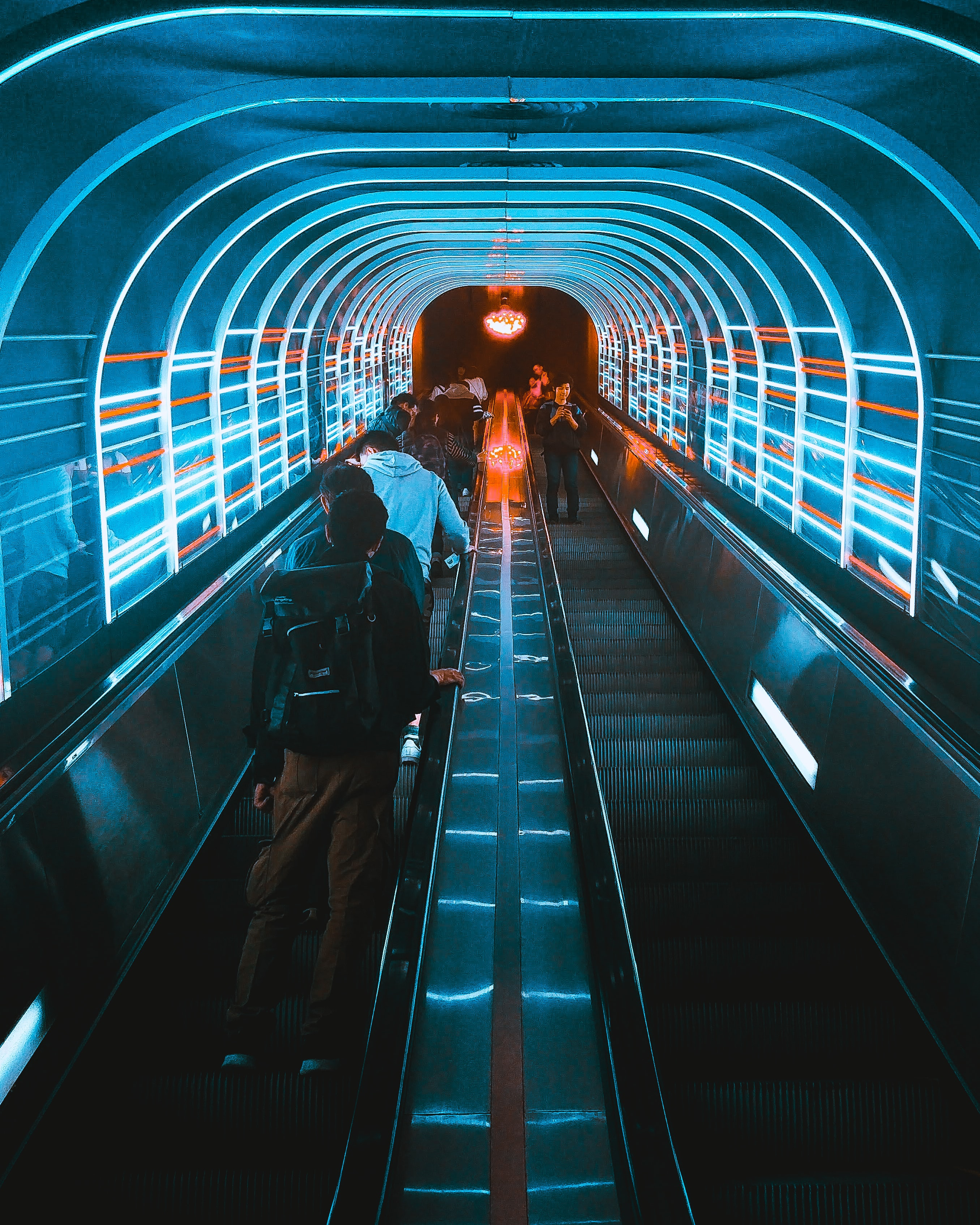photo of people using escalators under blue LED lights