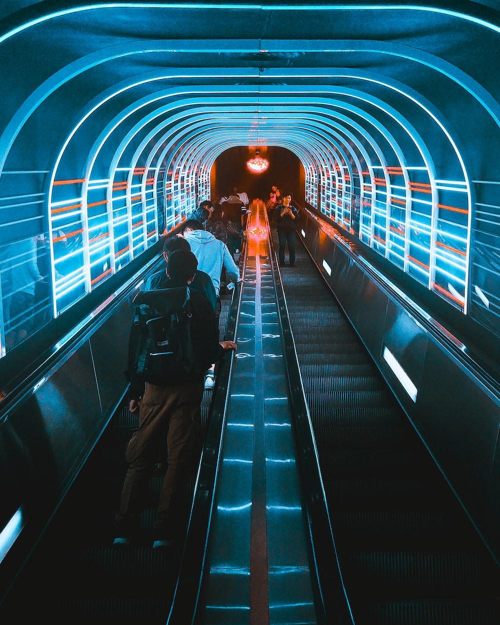 photo of people using escalators under blue LED lights
