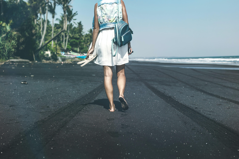 woman walking on the seashore during daytime