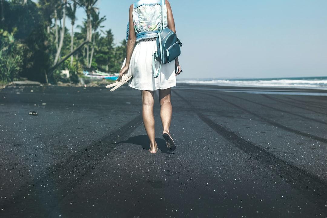 Young woman on a black sand beach, Bali island.