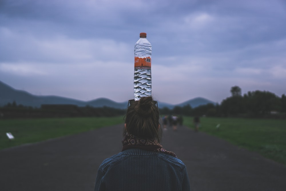 woman putting a clear plastic bottle on her head