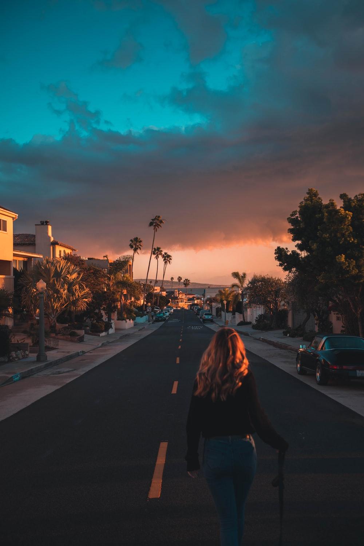 woman walking on grey and yellow asphalt road