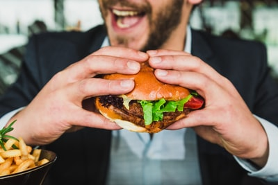 person holding burger bun with vegetables and meat lunch zoom background