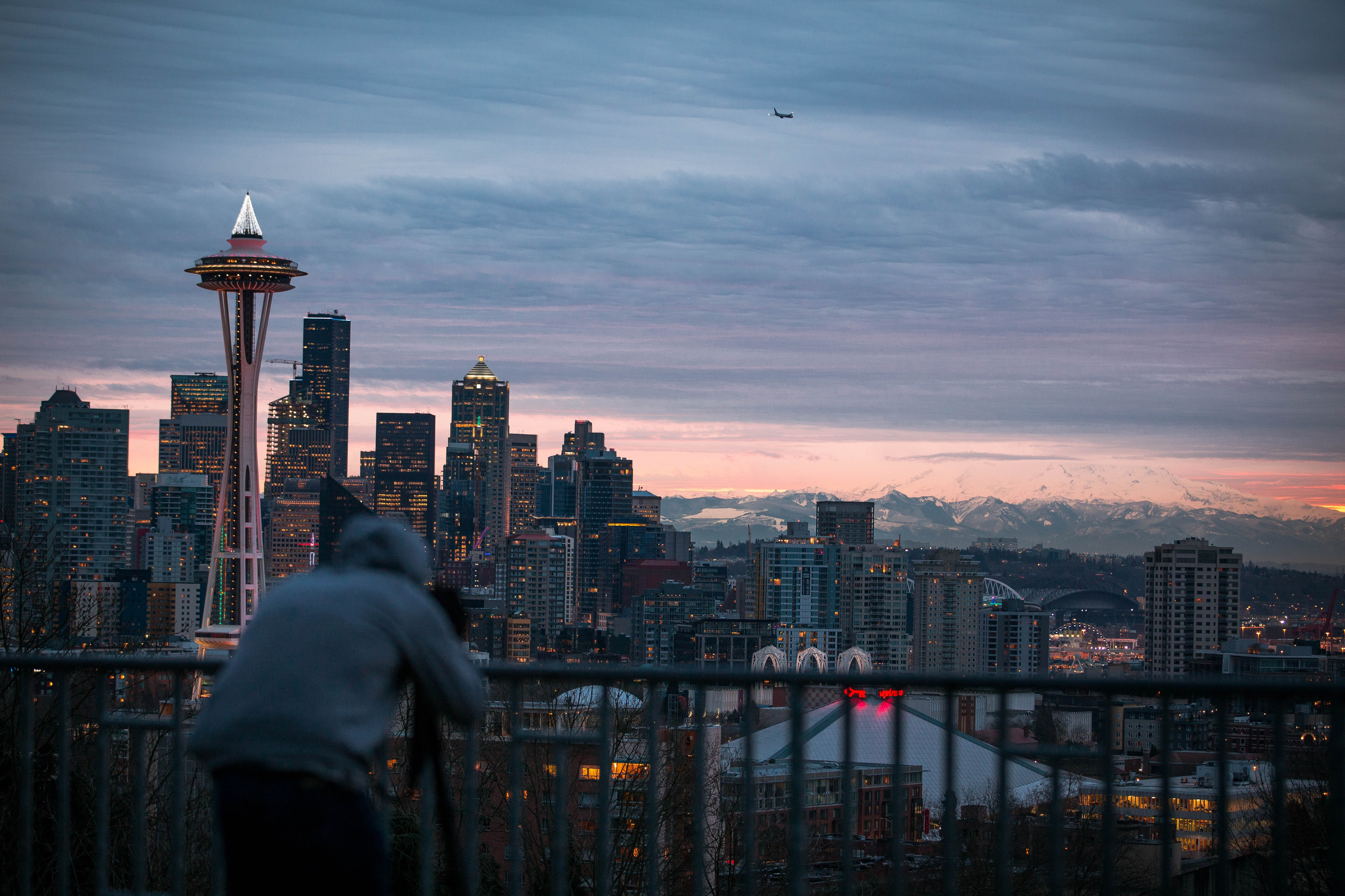 photo of person wearing grey pullover hoodie taking a photo of concrete buildings under cloudy sky