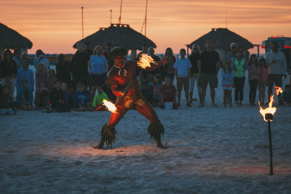 man dancing fire dance surrounded by people at beach