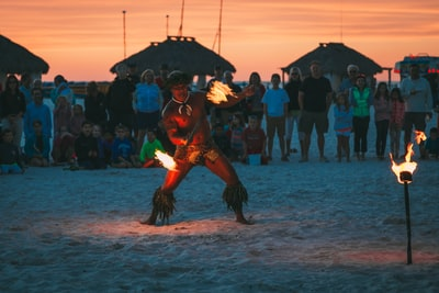 man dancing fire dance surrounded by people at beach dancer zoom background