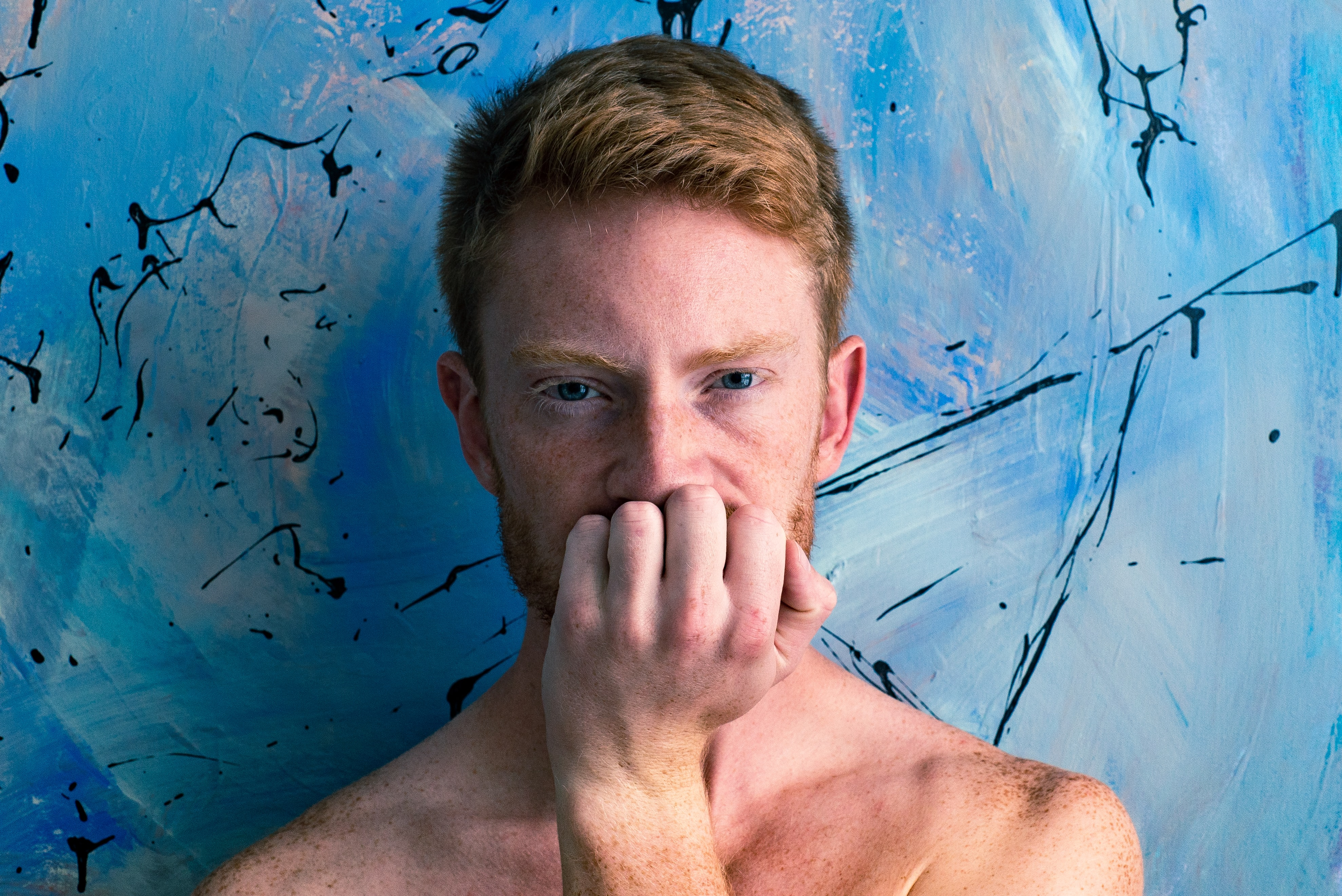man holding his chin with abstract painting background