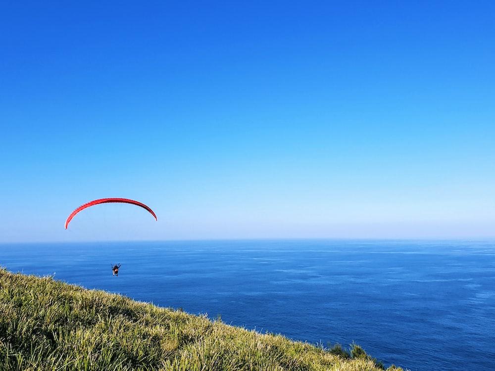 person parasailing on seashore