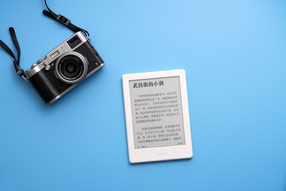 black SLR camera on and white e-book reader