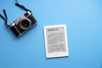 black SLR camera on and white e-book reader