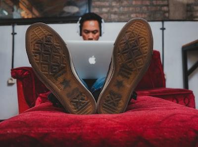 man using macbook on sofa boot zoom background