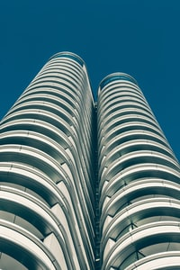 low angle photography of gray high-rise building under blue sky