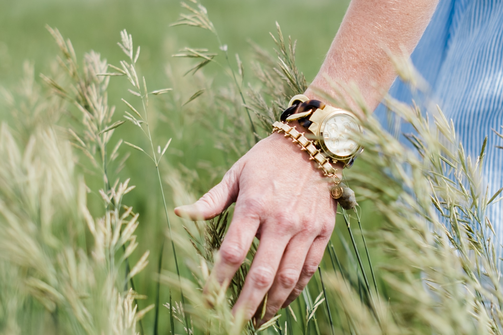 person wearing gold-colored analog watch with link bracelet