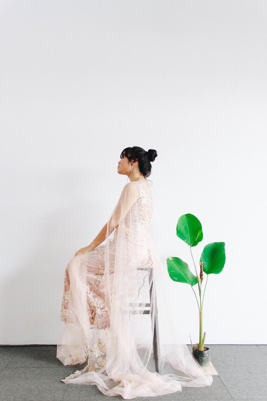 woman sitting on stool near leafed plant