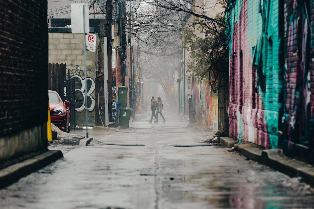 two women walking on alley