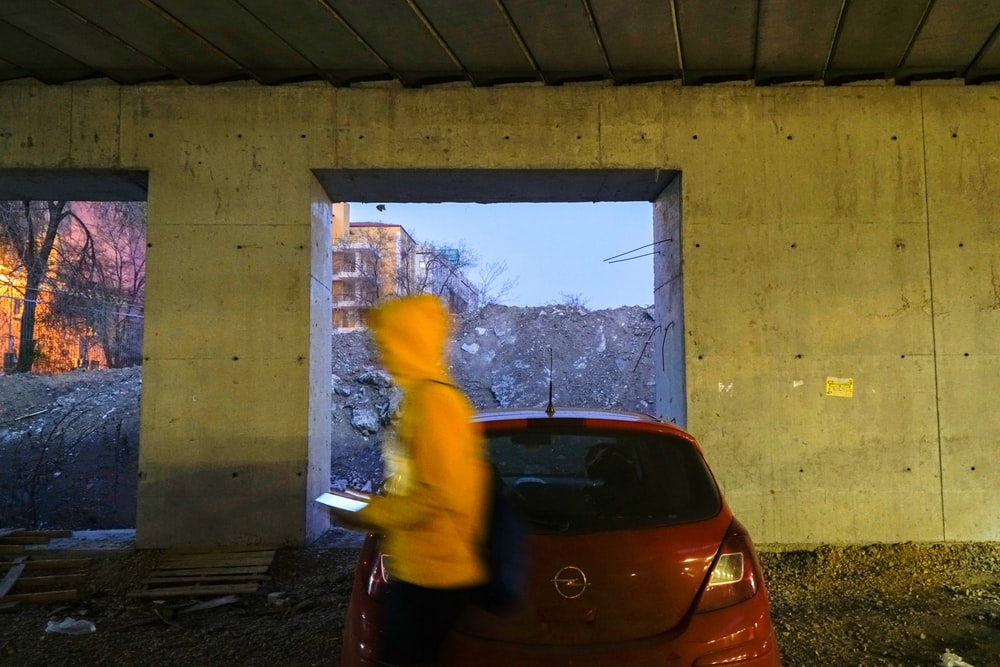 person wearing yellow hoodie near red Opel car