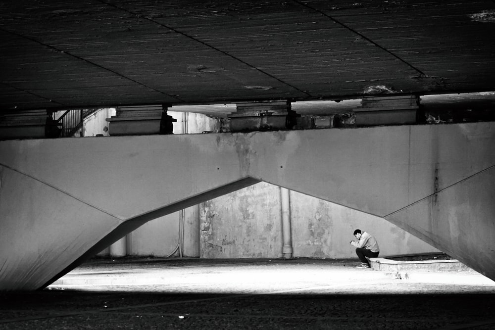 grayscale photography of man sitting under the bridge