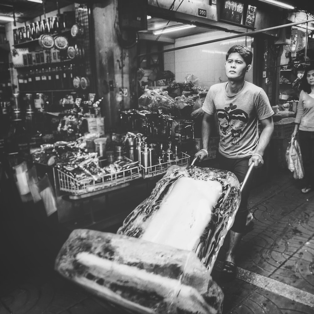 grayscale photo of man carrying ice block using hand truck