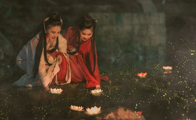 two women wearing white and red traditional dress holding flowers lantern festival teams background