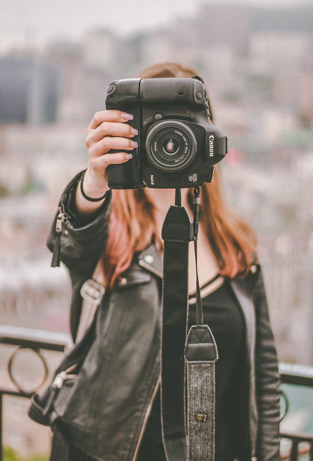 woman in black leather jacket holding black Canon DSLR camera