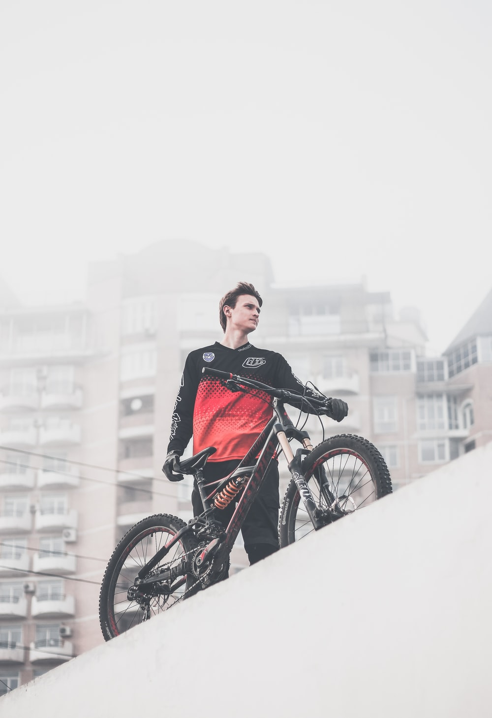 man wearing black and red ombre crew-neck long-sleeved shirt and black gloves standing on platform holding black full-suspension bike