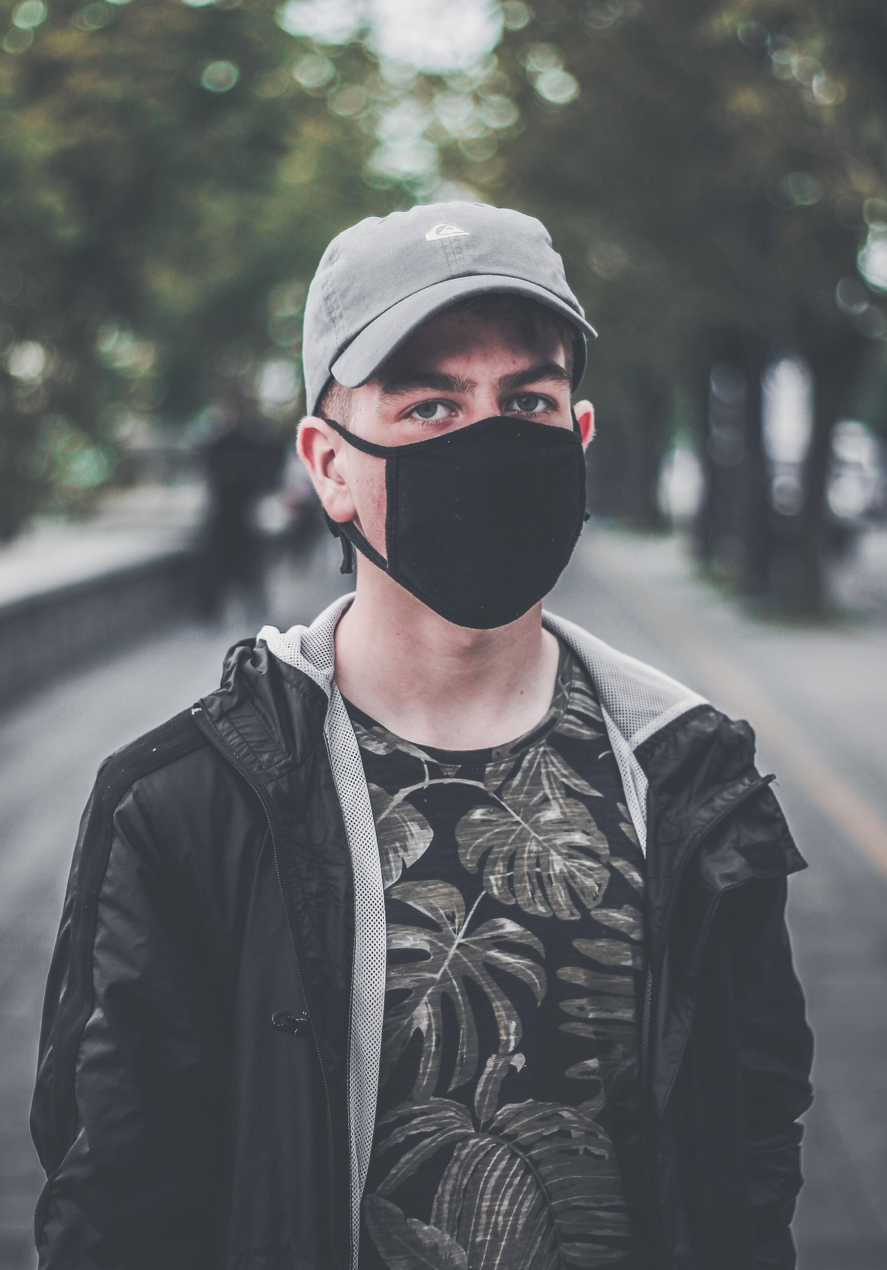 man wearing black face mask on park during daytime