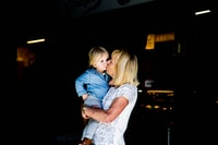 candid photography of woman carrying and kissing child