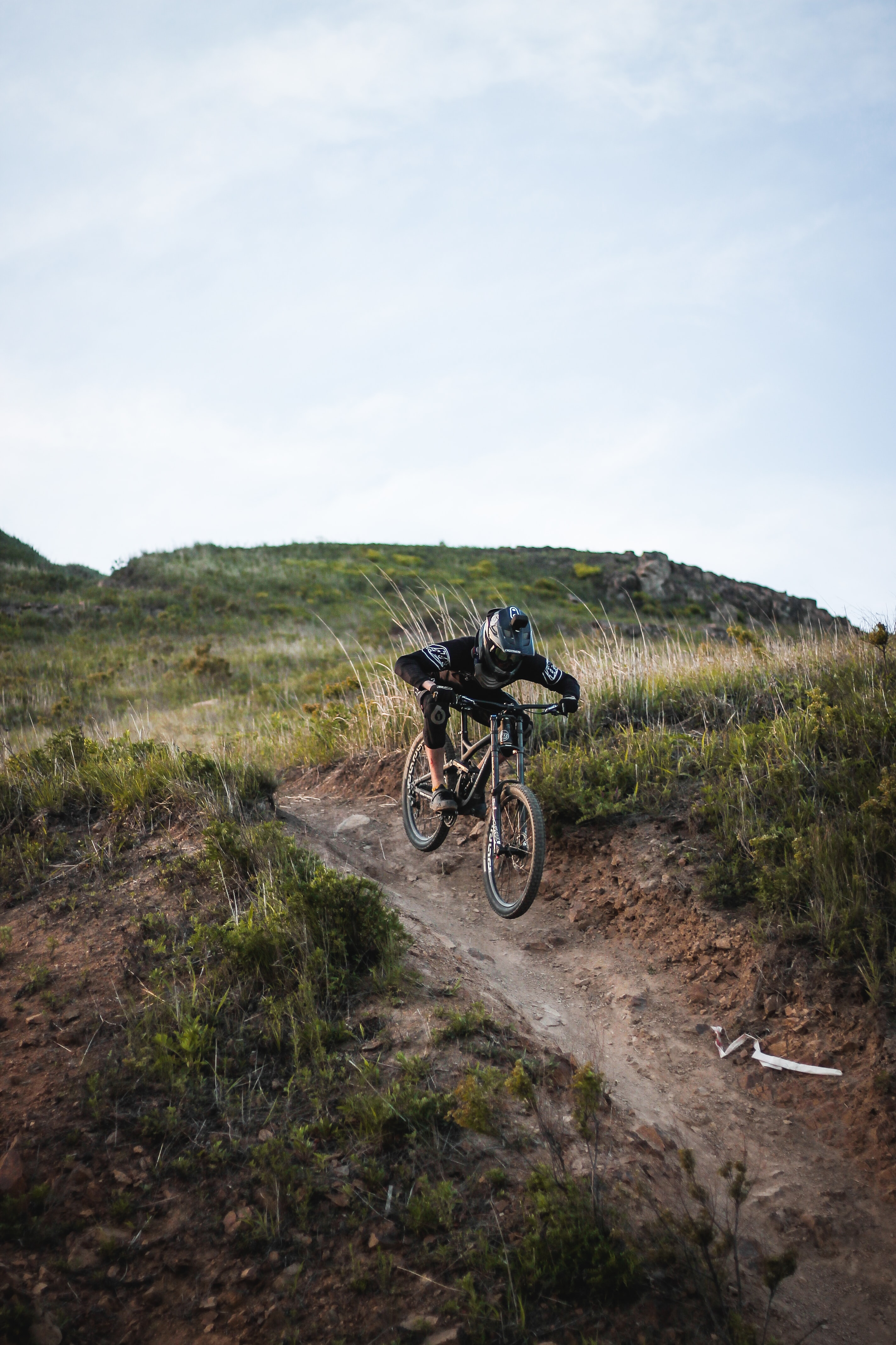 man riding mountain bike on hill under cloudy skies