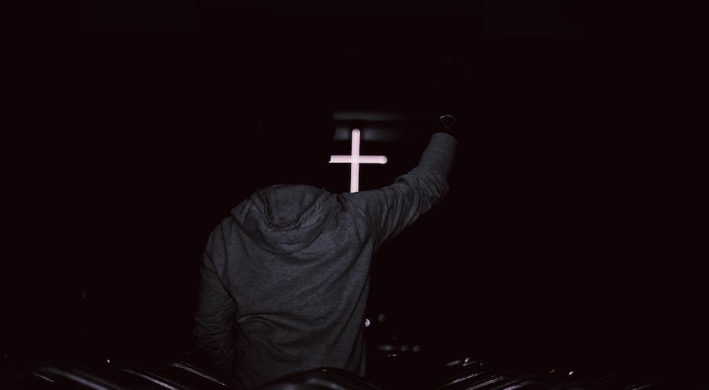man in gray hoodie jacket raising hand