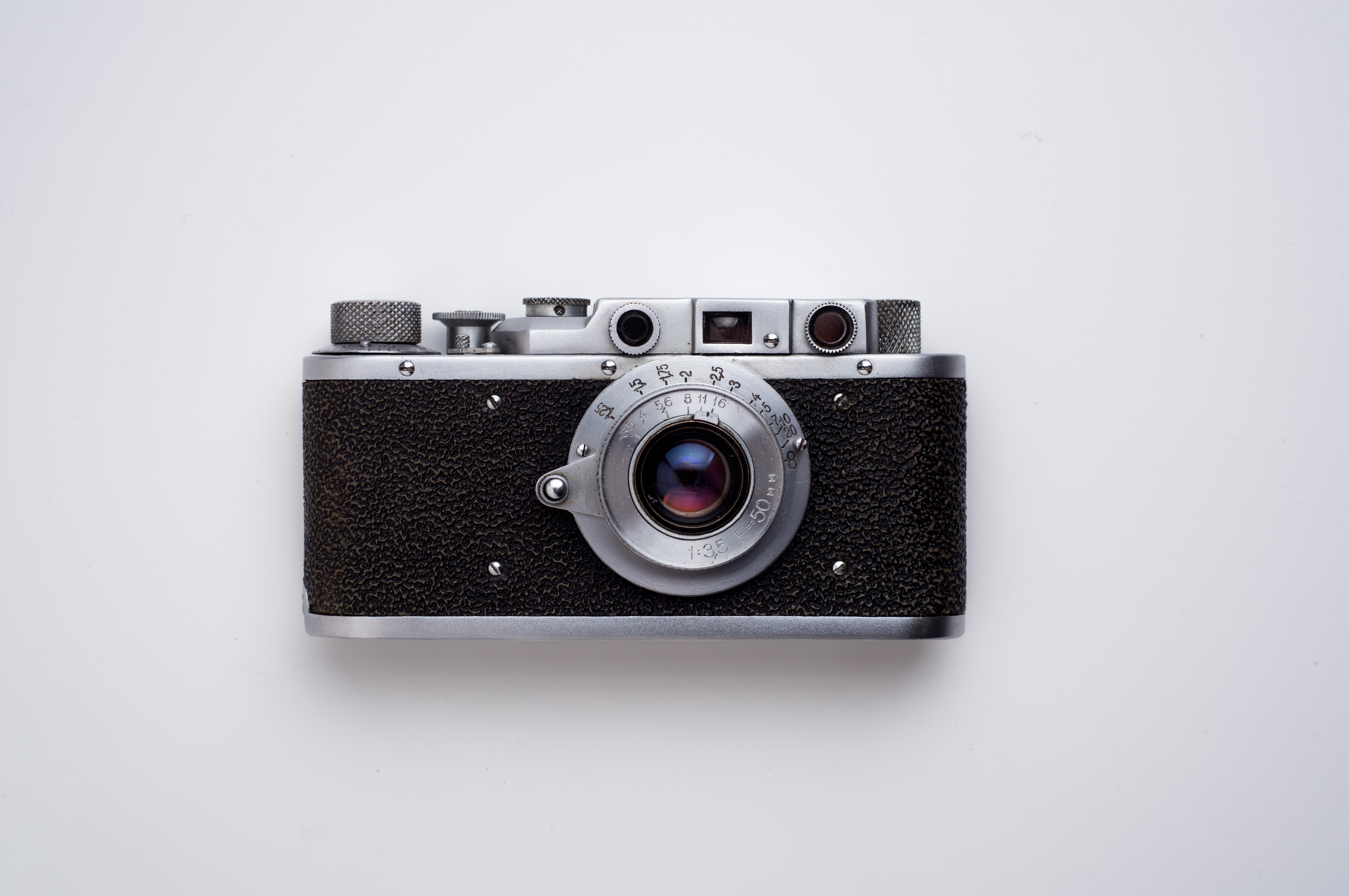 black and gray SLR camera on white background