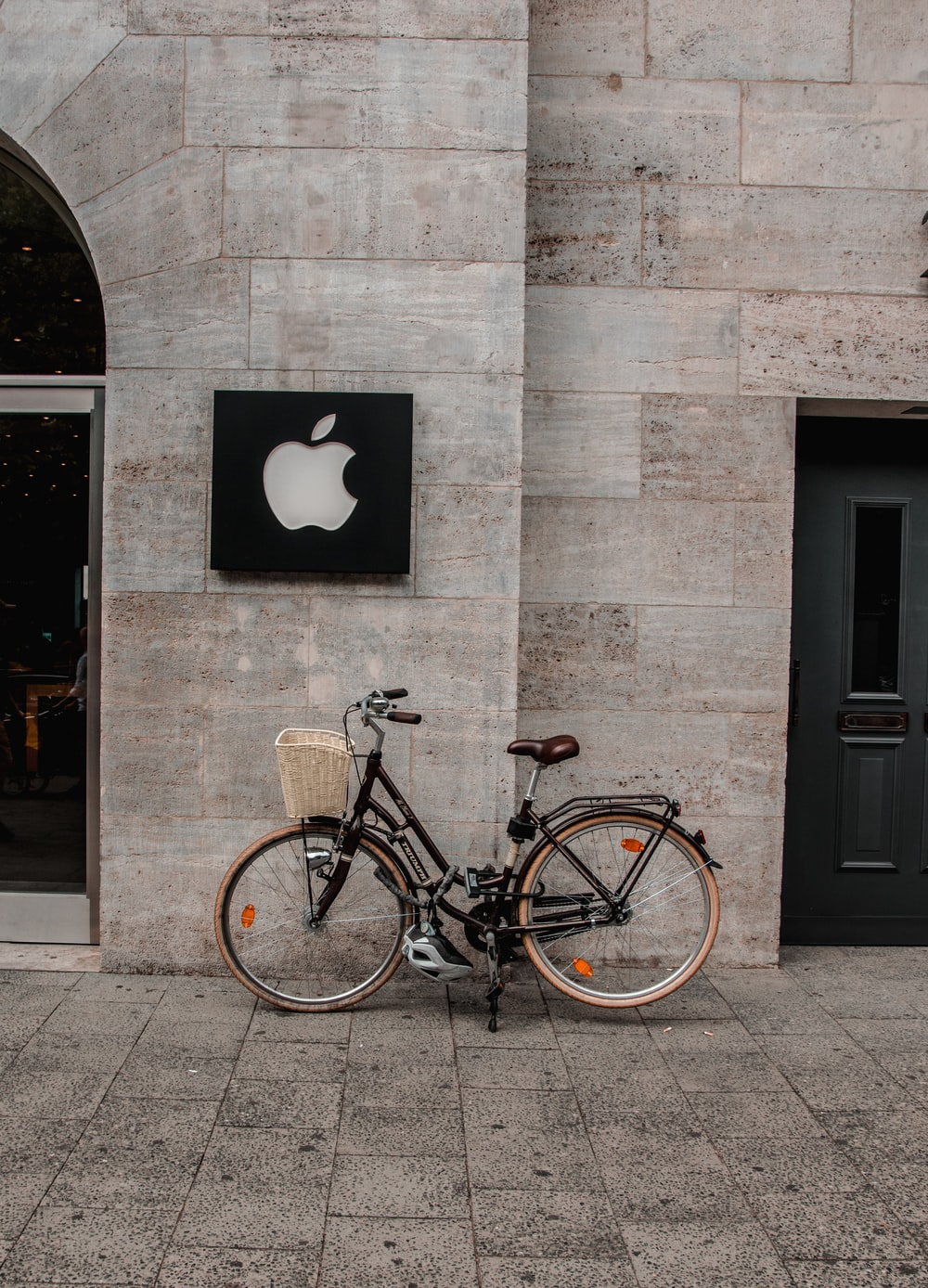 black commuter bicycle parked beside building