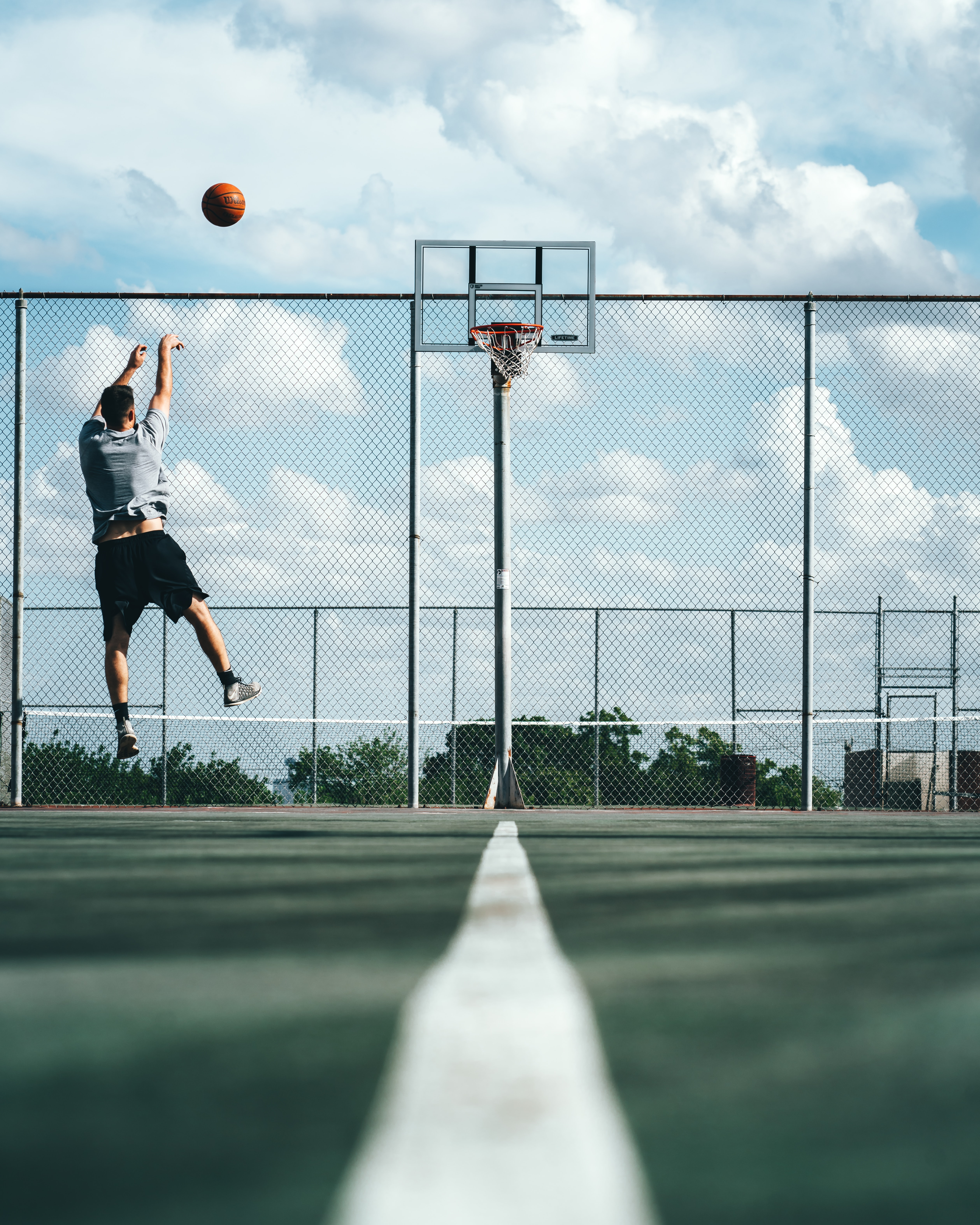 man shooting ball on basketball hoop