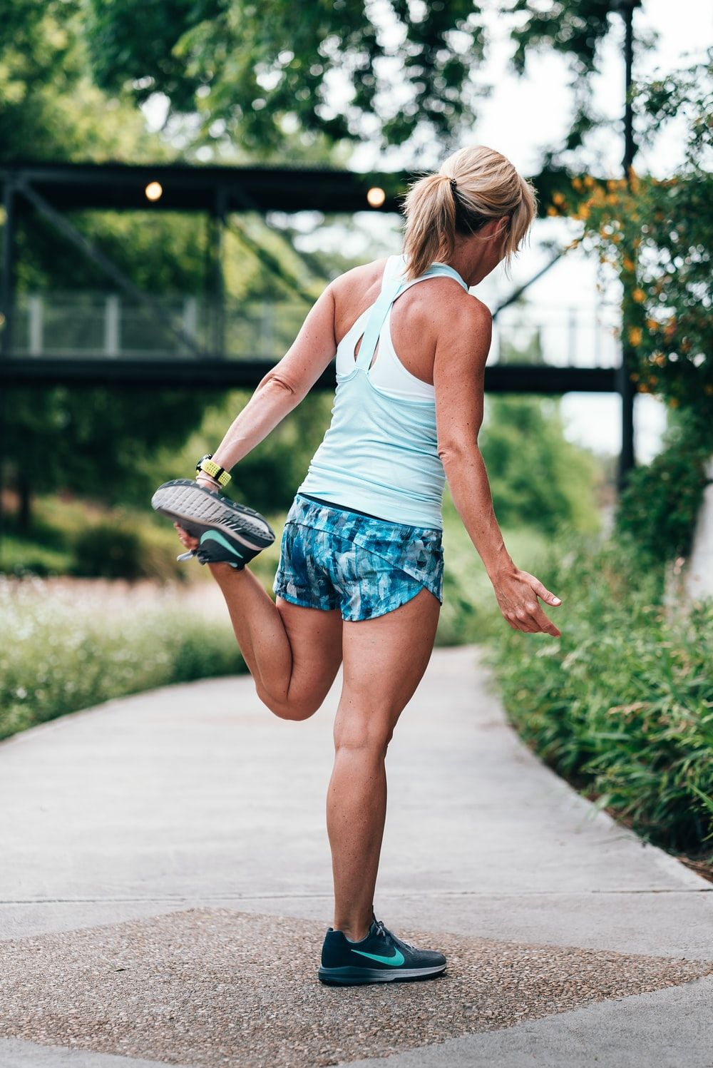 woman stretching on gray concrete pathway