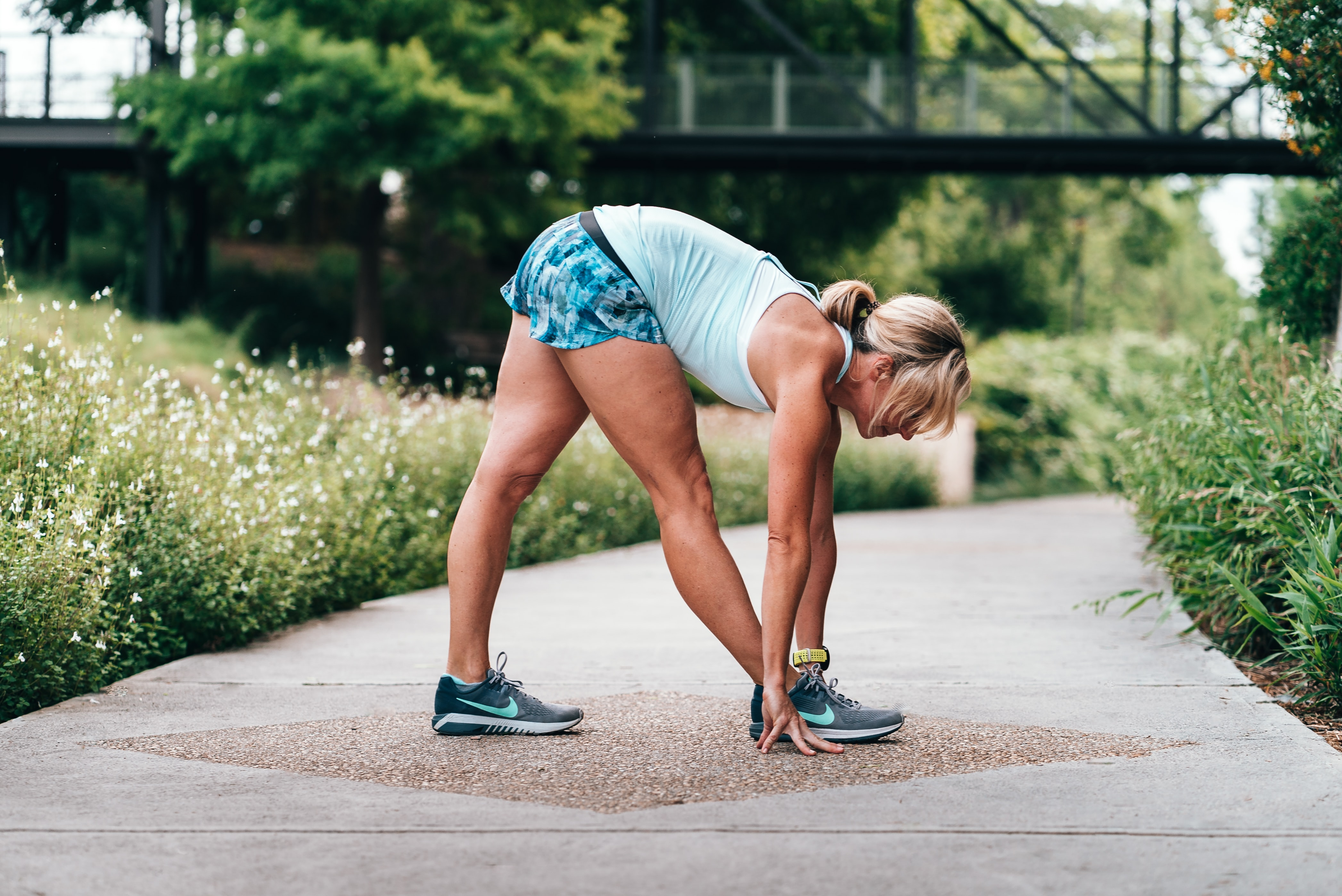 woman stretching on gray concrete pathway near green grass