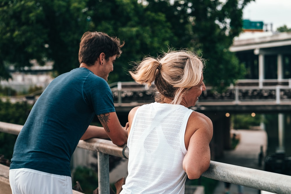 man and woman standing near the railings