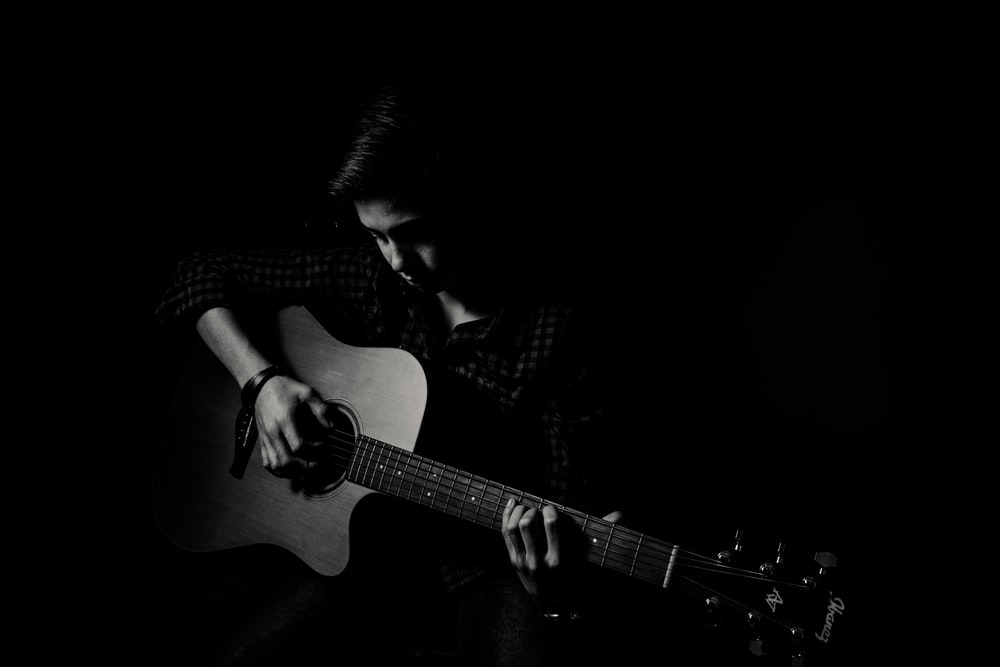 man playing guitar on black background