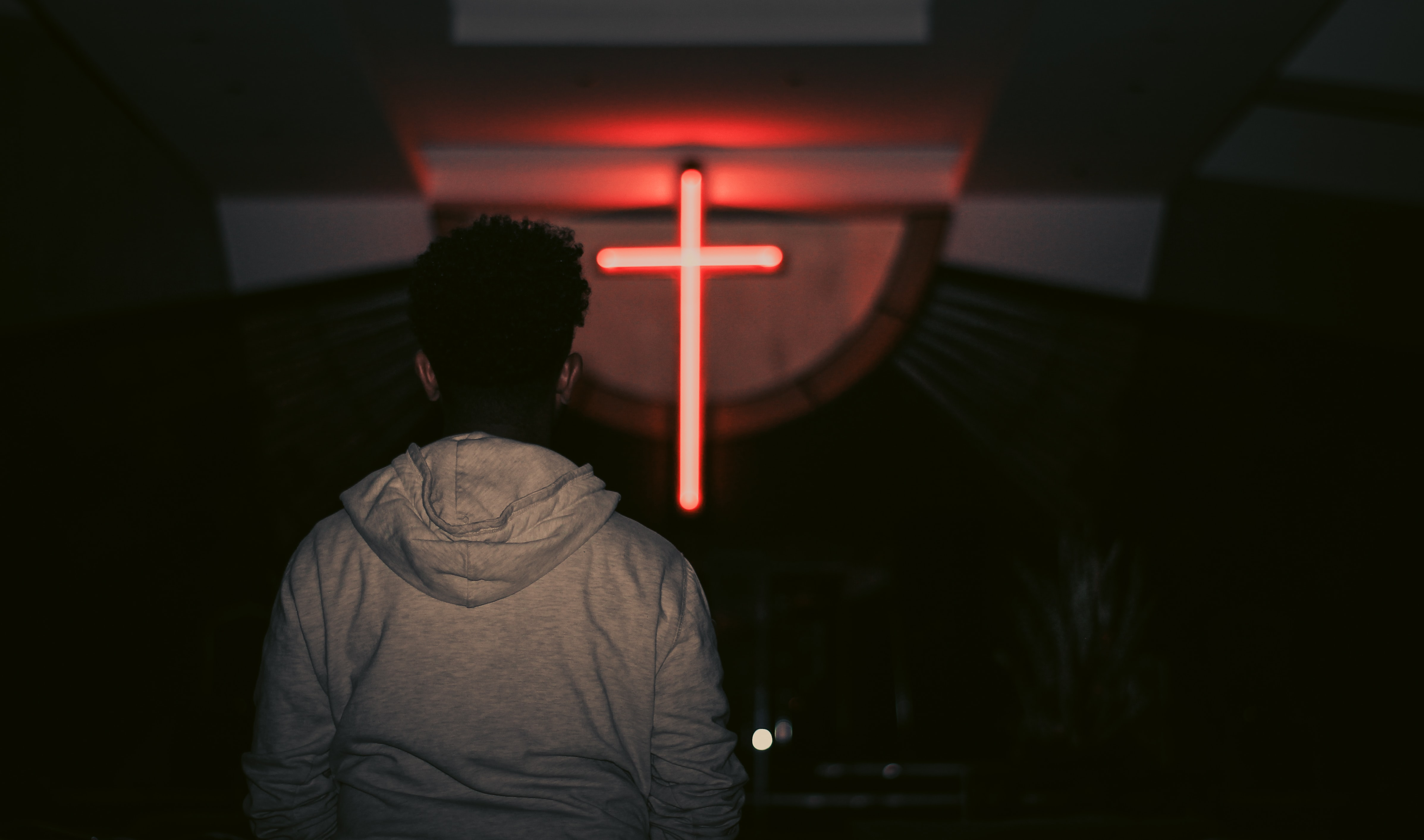 man facing red LED cross