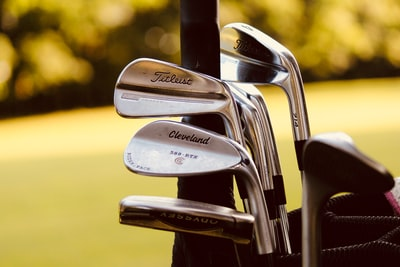 gray steel golf clubs on selective focus photo golf teams background