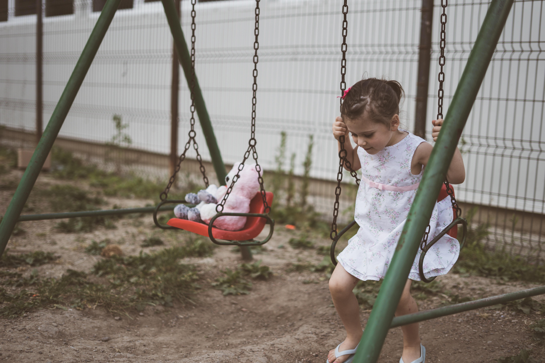 girl sitting on swing playset
