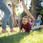 woman in white blouse and blue denim jeans helping a baby crawl on green grass
